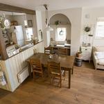 白くペイントされた板壁に囲まれたキッチン。柱やガラスのシェードがカフェの雰囲気を演出。サイドに設けた机は、ママの仕事スペース。