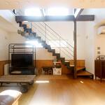 腰壁を配した木質な内装と黒アイアンの階段がバランスよく