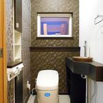 シックなブラウンを基調としたクロス、手洗い場のボールにも奥様こだわりがみえるトイレとなりました。 トイレの扉は折れ戸で、車いすも入れる大きな扉となっているため、活用しつつ手洗いカウンターが邪魔をしないようにデザイン性のあるカットラインを設計士と共に工夫しました。